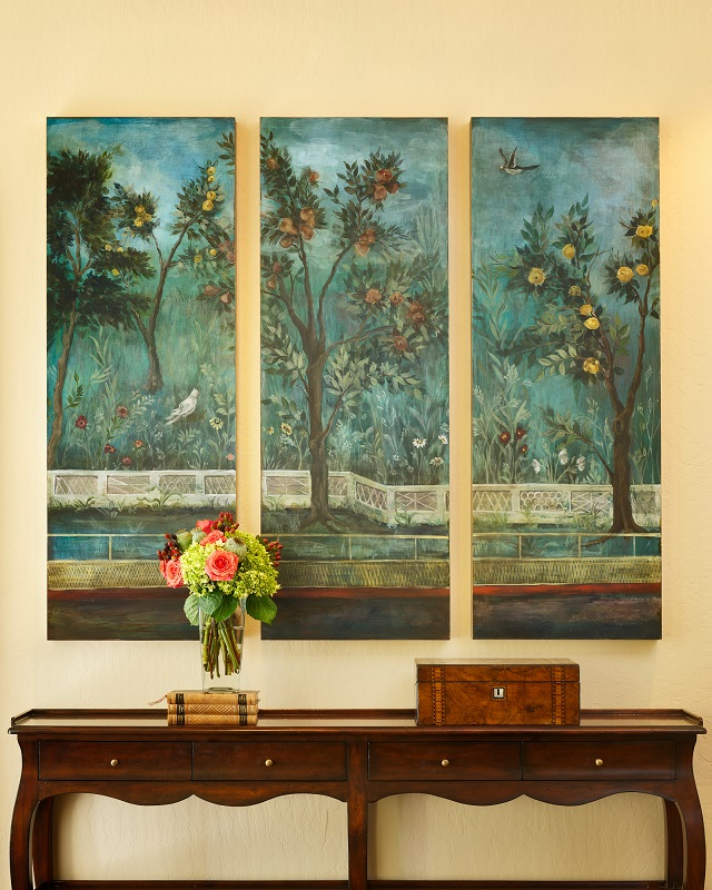 Beautifully crafted, a retail sideboard in the entryway sits beneath commissioned artwork by Katherine Jacobus.