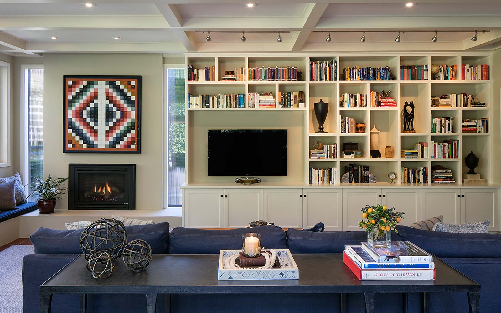 Looking over a blue sofa to a large built-in book shelf with a TV hung on the left.