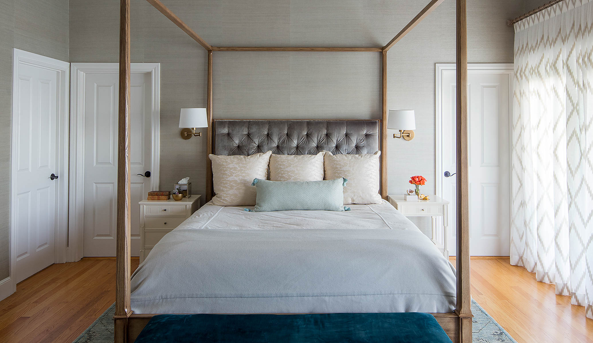 A four poster bed with nightstands on either side.