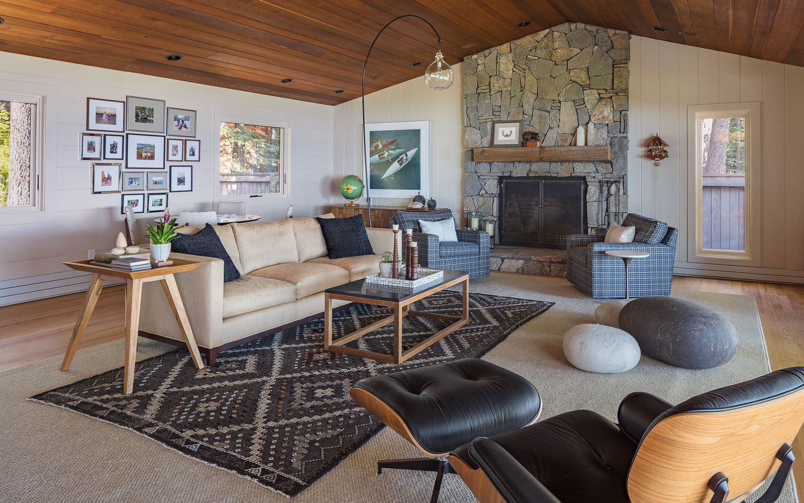 A living room with a beige sofa, stone fireplace, and stylish decor.