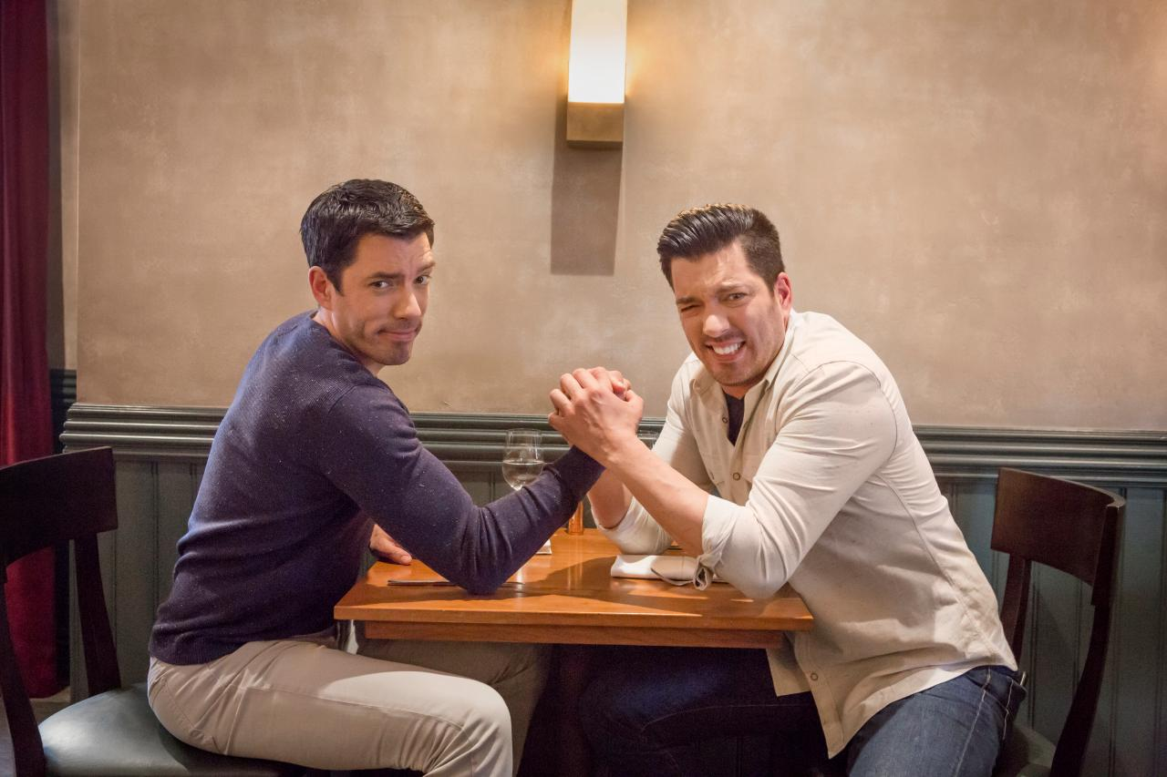 Two men arm wrestling at a table.
