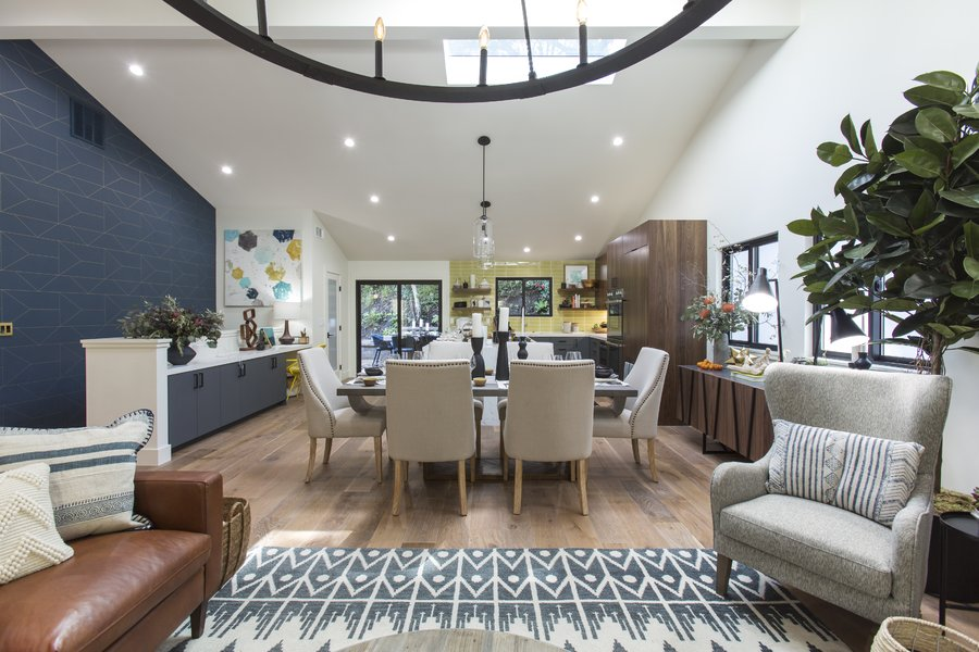 View of an open concept living room / dining room / kitchen. A blue and gold accent wall is on the left.
