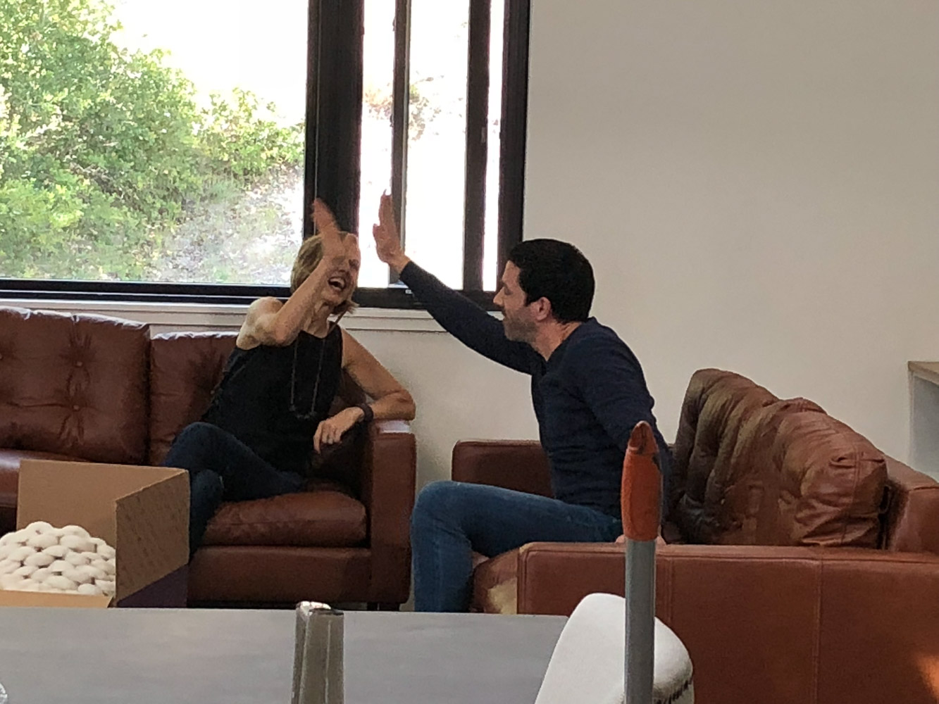 A woman and a man high fiving on two leather sofas.