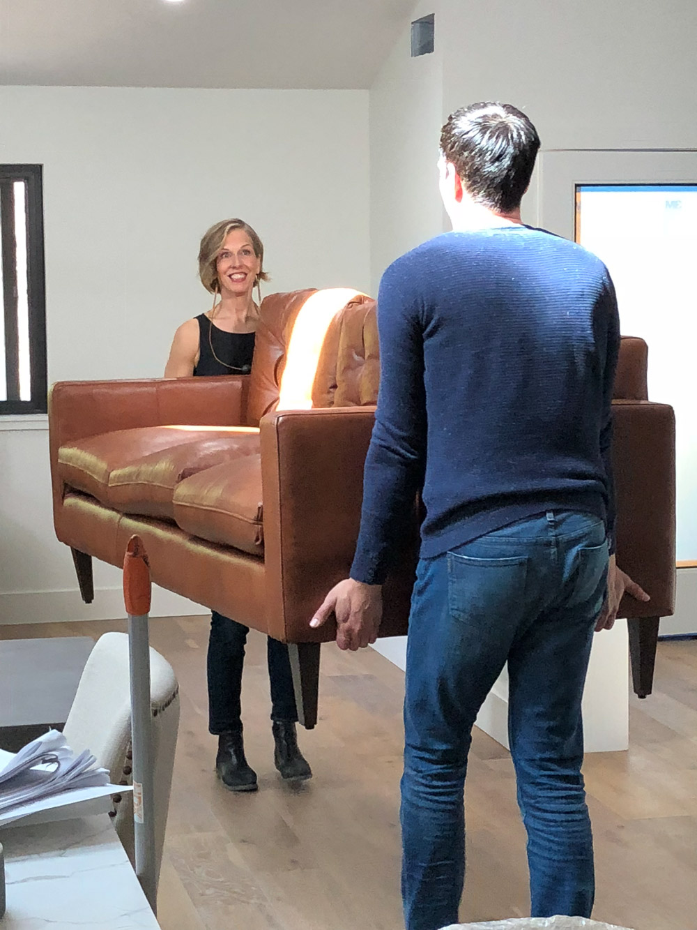 A woman and a man moving a brown leather sofa.