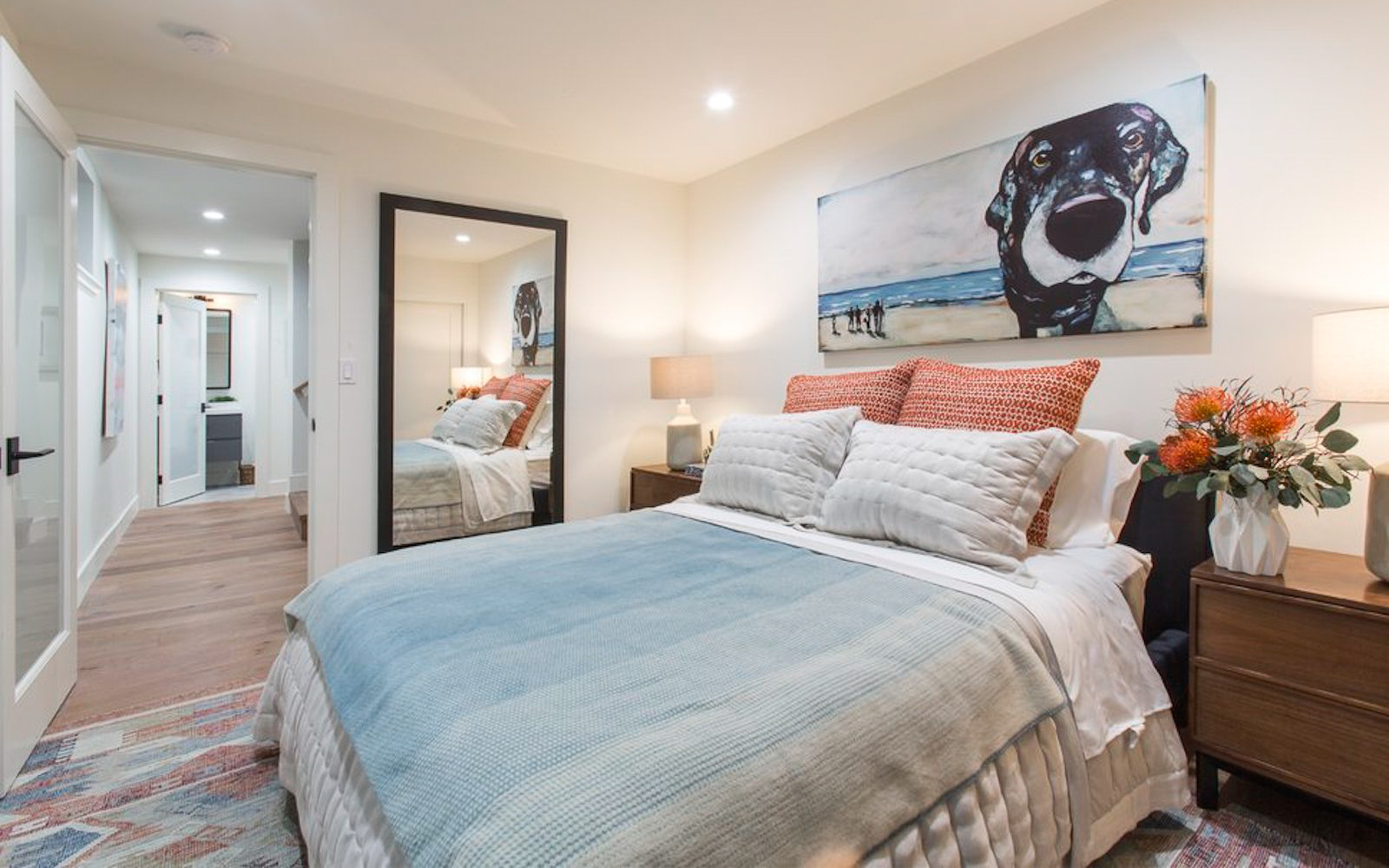 A styled bedroom with a large bed in the center and an illustration of a dog hanging above it.