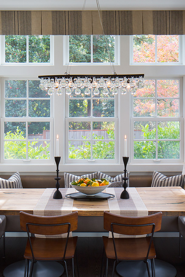 View of a dining nook. A chandelier hangs over the center of the dining table.
