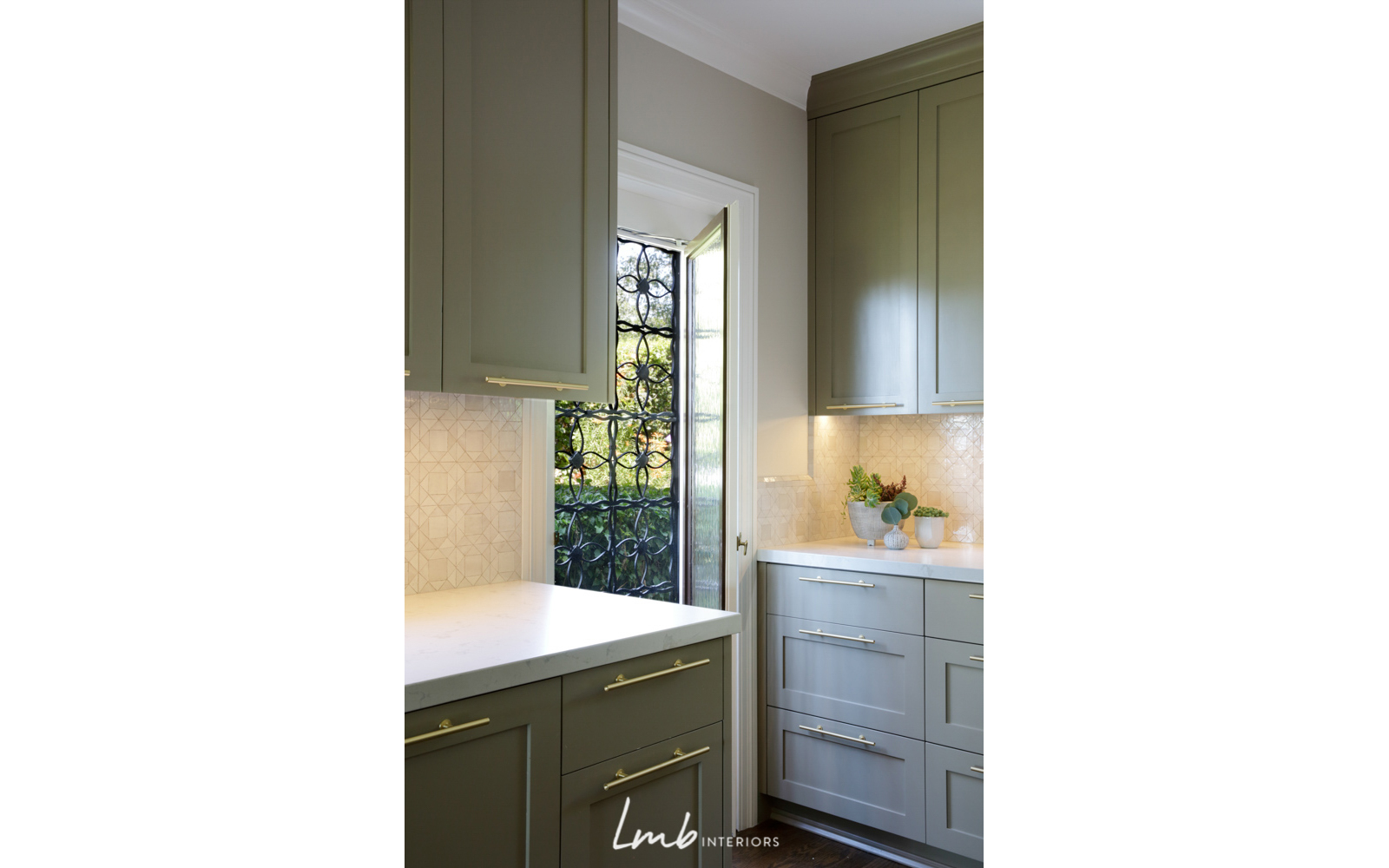 "Kitchen features that pop: Handcrafted wrought-iron ""screen"" door, Mosaic House tile backsplash, gold-tone accents"